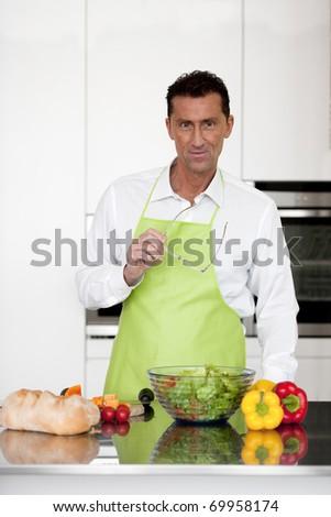 Mature man preparing food in his kitchen - stock photo
