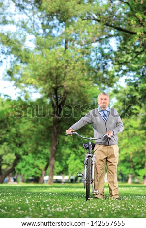 Mature man pushing a bicycle in a park