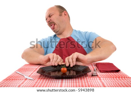 Mature man pushing away his plate with a little tomato - stock photo