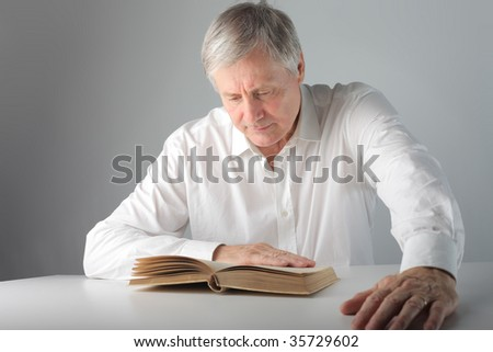 mature man reading a book - stock photo
