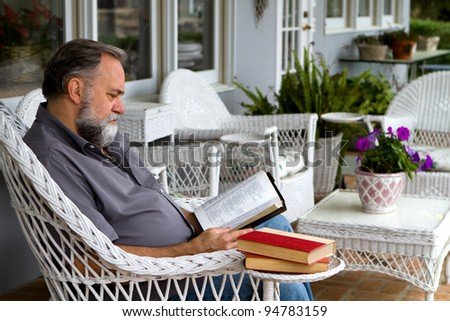 Mature man reads his bible while sitting in a white wicker chair on a porch. - stock photo