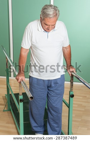 Mature man rehabilitating his legs - stock photo