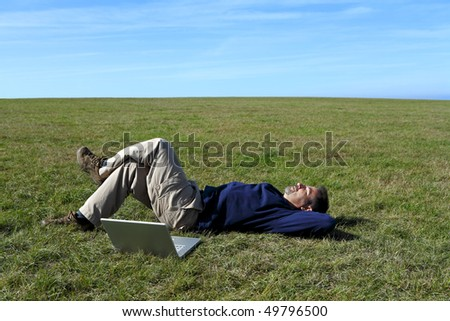 Mature man relaxing in field next to laptop - stock photo