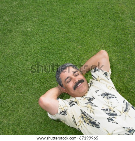 Mature man relaxing on green lawn