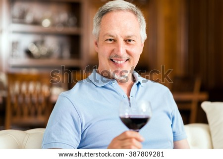 Mature man relaxing with a glass of red wine - stock photo