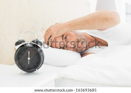 Mature man resting in bed with alarm clock in foreground at bedroom