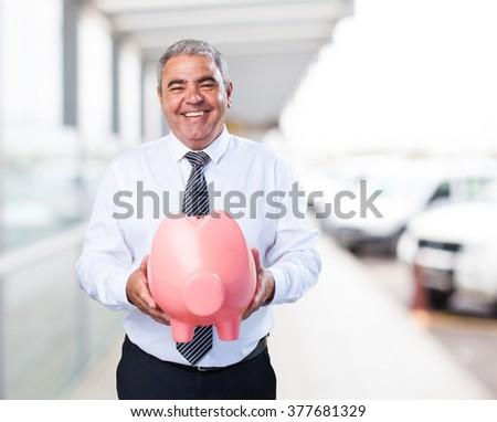 mature man saving with piggy bank - stock photo