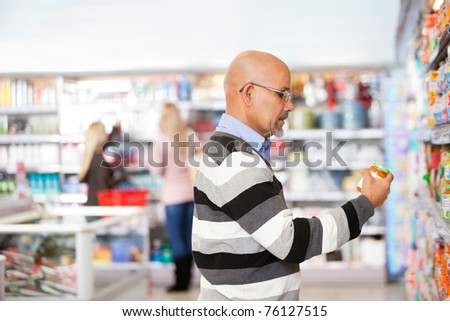 Mature man shopping in the supermarket with people in the background - stock photo