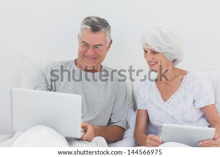 Mature man showing something on his laptop to his wife on bed - stock photo