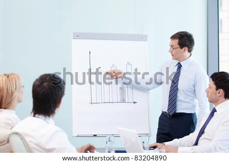 Mature man shows a graph of the staff - stock photo