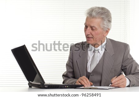 mature man sitting at the computer on a background