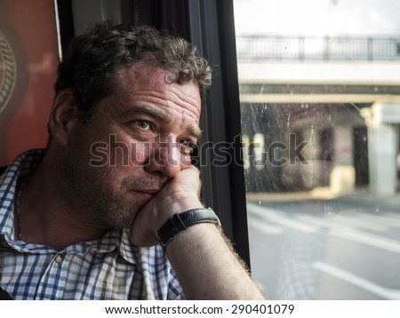 Mature man sitting at the window a public bus.