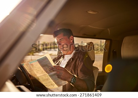 Mature man sitting in the driver's seat of his car, looking at a map in confusion while he is trying to figure out directions for his journey. The shot has been taken from outside of the vehicle - stock photo