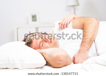 Mature man sleeping in bed with his wife - stock photo