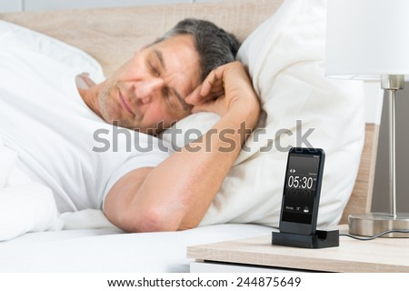 Mature Man Sleeping On Bed With Alarm On A Digital Cell Phone Display - stock photo