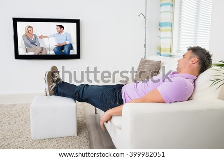 Mature Man Sleeping On Sofa While Watching Television At Home