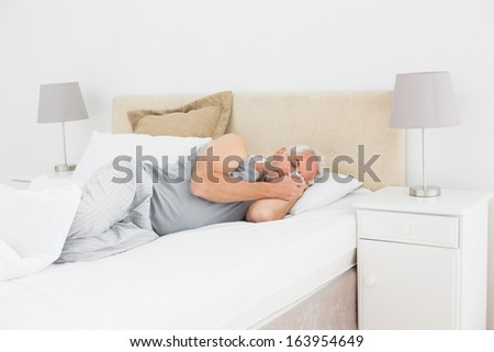 Mature man sleeping peacefully in bed at home