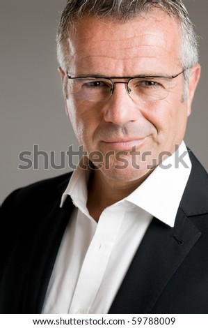 Mature man smile with satisfaction with his new eyeglasses and looking at camera - stock photo