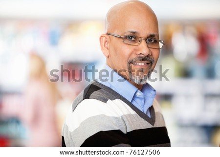 Mature man smiling while shopping in the supermarket - stock photo
