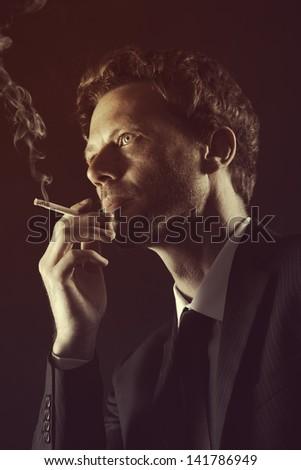 Mature man smoking cigarete against black background - stock photo