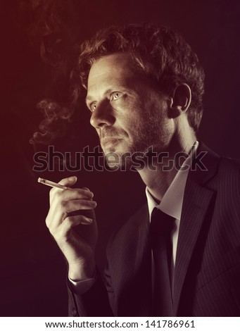 Mature man smoking cigarete against dark background - stock photo