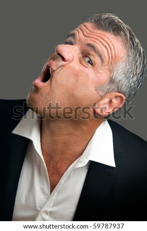 Mature man splattered behind a glass window with suffering and funny expression - stock photo