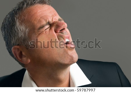 Mature man splattered behind a glass window with suffering expression - stock photo