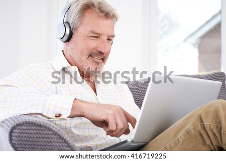 Mature Man Streams Music From Laptop To Wireless Headphones - stock photo