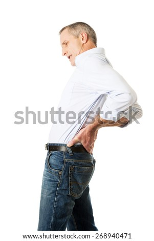 Mature man suffering from back pain. - stock photo