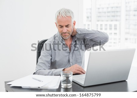 Mature man suffering from neck ache while using laptop at desk in a bright office