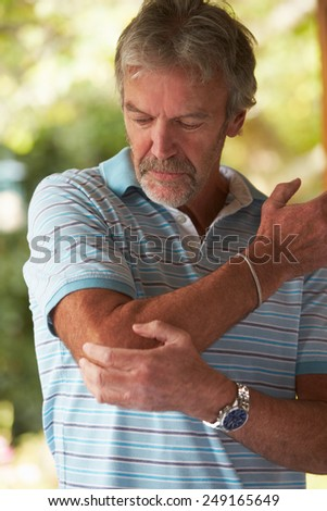 Mature Man Suffering From Painful Elbow At Home - stock photo
