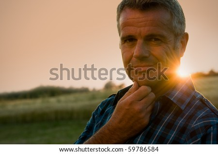 Mature man taking a break and relax in a meadow in the wonderful warm light of the sunset - stock photo