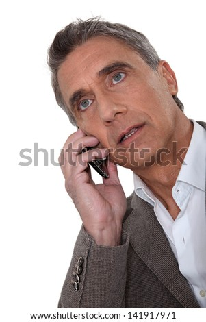 Mature man talking on a cellphone - stock photo