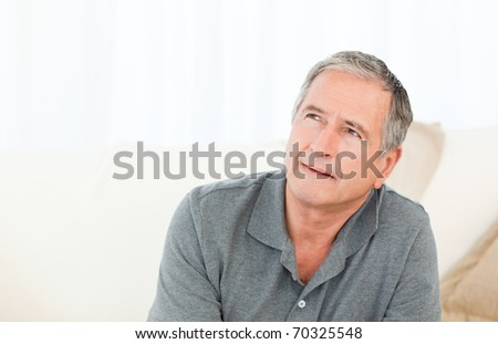Mature man thoughtful with his walking stick on his bed at home