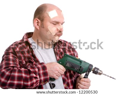 Mature man trying to drill something covered in bandaids - stock photo