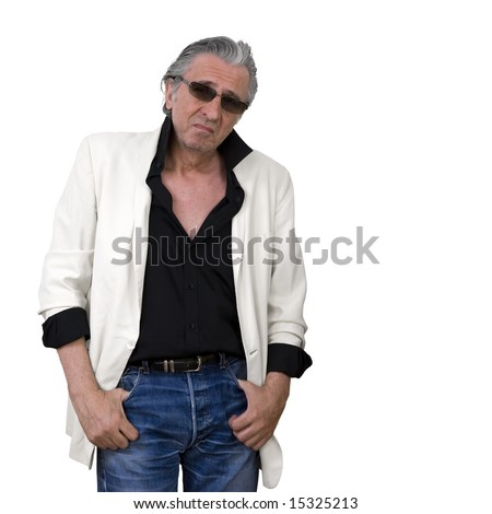 Mature man wearing a white tuxedo and sunglasses standing and looking at the camera. - stock photo