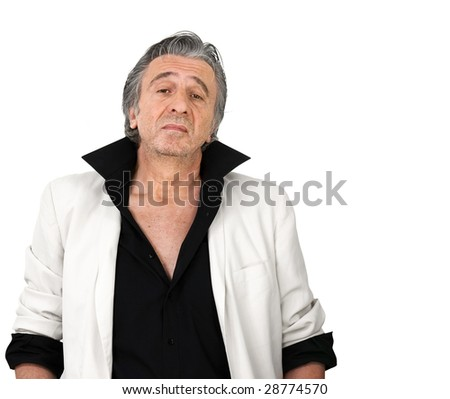 Mature man wearing a white tuxedo standing and looking at the camera. - stock photo