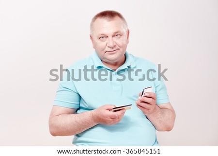 Mature man wearing blue shirt holding mobile phone and credit card in his hands against white wall - mobile payment concept - stock photo