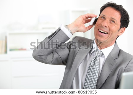 mature man wearing grey suit with tie is laughing - stock photo