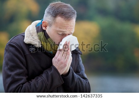 Mature man wearing jacket suffering from cold - stock photo