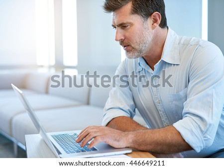 Mature man with a handsome short beard, sitting in a business lounge, typing on his laptop - stock photo