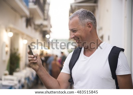 Mature man with backpack looking at his smart phone for directions and location.