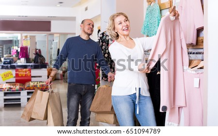 Mature man with bags waiting for happy woman selecting dress in boutique