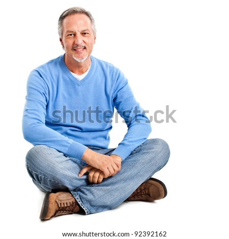 Mature man with casual look sitting on the floor isolated on white - stock photo