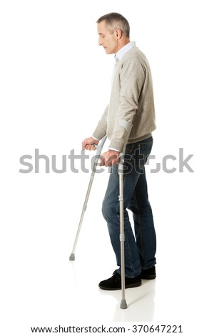 Mature man with crutches - stock photo