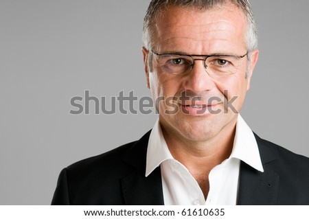 Mature man with eyeglasses looking at camera and smiling - stock photo