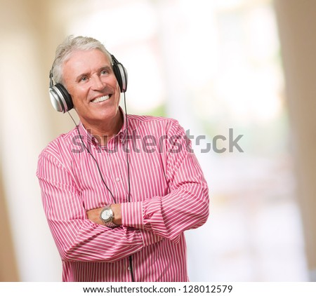 Mature Man With Headphones against an abstract background - stock photo