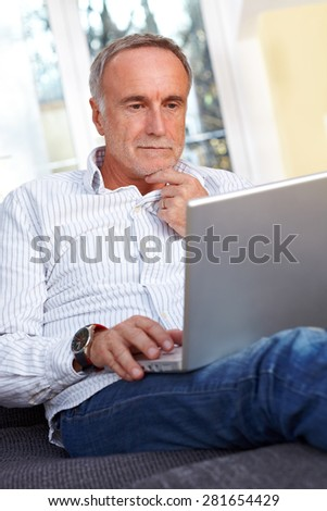 mature man with laptop, thinking