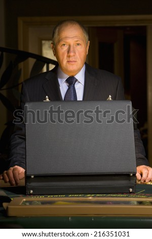 Mature man with open briefcase at poker table, portrait