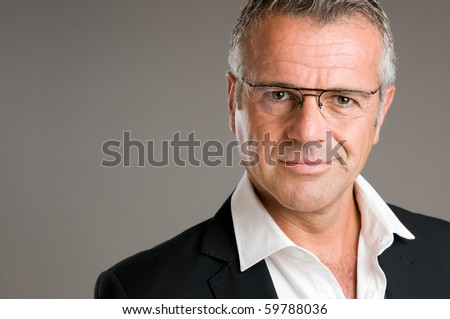 Mature man with pair of glasses looking at camera with satisfaction - stock photo